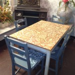 Blue distressed chairs with light wood stained table both done in paisley stencil.